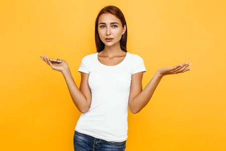 Confused girl with a mobile phone in her hands, depicts a misunderstanding on a yellow background