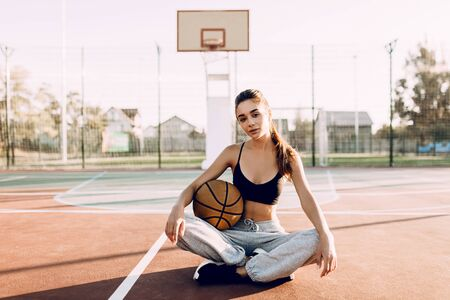 Attractive young athletic girl holding a basketball while sitting in a sports stadium, outdoors. Rest after training Stock Photo