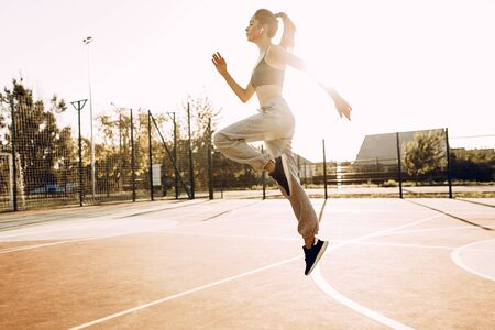 Attractive young sportswoman exercising outdoors in headphones, jumping Stock Photo