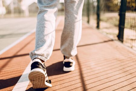 Close - up of women's sports legs with sneakers, legs sports man, athlete in a running pose on the street. morning jog Stock Photo