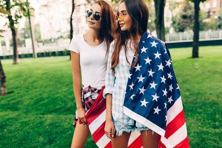 Dos chicas atractivas con estilo con una bandera estadounidense se divierten caminando en el parque en el verano