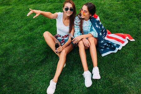 Dos atractivas chicas jóvenes con gafas de sol sentadas en el parque en el césped con la bandera estadounidense, con una bebida refrescante. Celebraciones del día de la independencia de EE. UU.