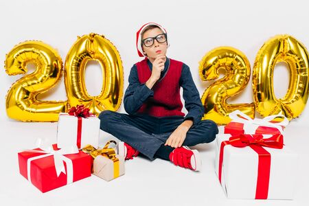 Pensive little boy in Santa hat, stylish child sits pensive with Christmas gifts sitting on white background with gold 2020 digits. The Concept Of The New Year 2020