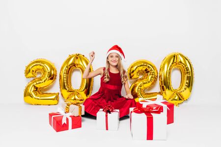 Happy little girl in Santa hat, stylish baby rejoices Christmas gift by showing victory gesture while sitting on white background with gold 2020 numbers. The Concept Of The New Year 2020
