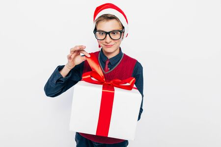 Happy boy in a red Santa hat. Stylish boy with Christmas gift, joyfully opens Christmas gift, on white background. Christmas and New year concept 版權商用圖片