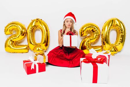 Pensive little girl in Santa hat, stylish baby sitting pensive with Christmas gifts sitting on white background with gold 2020 numbers. The Concept Of The New Year 2020