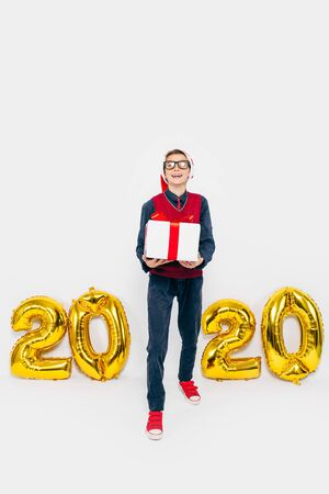2020 New year A little boy in a Santa hat, a stylish child with a Christmas gift in his hands, on a white background with gold figures 2020. The Concept Of A New Year