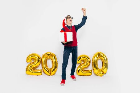 2020 New year A little boy in a Santa hat, and with a gift in his hands, a stylish child is enjoying a Christmas gift, on a white background with gold figures 2020. The Concept Of A New Year Фото со стока