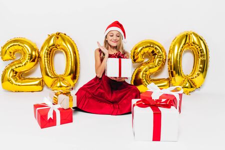 Happy little girl in Santa hat, stylish baby sitting with Christmas gifts sitting on white background with gold 2020 numbers. The Concept Of The New Year 2020