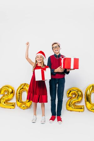 Happy little girl and boy, wearing Santa hat, stylish brother and sister, holding Christmas gifts, and show victory gesture while looking at camera, on white background with gold 2020 figures. The Concept Of The New Year 2020