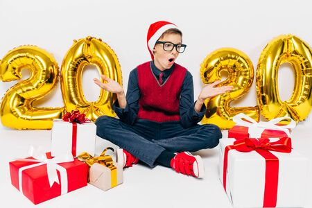 Happy little boy in Santa hat, stylish child delighted with Christmas gifts sitting on white background with gold figures 2020. The Concept Of The New Year 2020