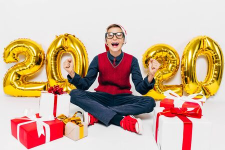Happy little boy in Santa hat, stylish child delighted with Christmas gifts, shows victory gesture sitting on white background with gold figures 2020. The Concept Of The New Year 2020