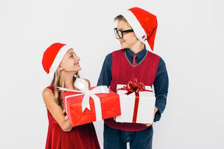 Happy little girl and boy in Santa hat, stylish brother and sister are rejoicing and giving each other Christmas gifts, on white background. The concept of the New year holiday