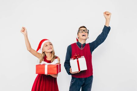 Happy little girl and boy in Santa hat, stylish brother and sister, rejoice holding Christmas gifts in their hands, and show victory gesture standing on white background. The Concept Of A New Year, Christmas