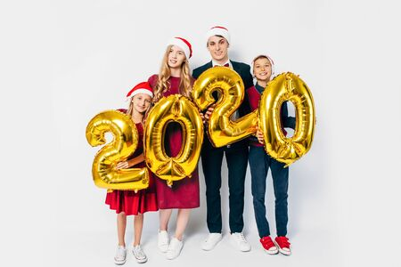 Young happy family with kids wearing Santa hats holding balloons shaped like numbers 2020 on white background. New year, Christmas, holiday