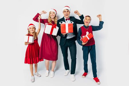 Young happy family Christmas with the kids in Santa hats, fun by showing the gesture of victory, holding Christmas gifts in hands on white background. New Year, Christmas, holiday