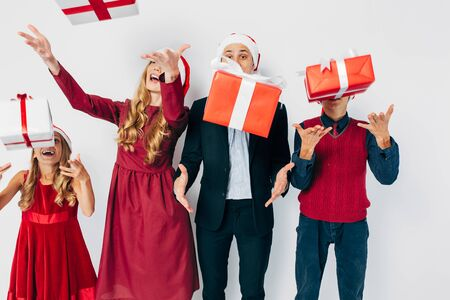 Young happy Christmas family with kids wearing Santa hats enjoying their presents by tossing Christmas gifts up on white background. New Year, Christmas, holiday