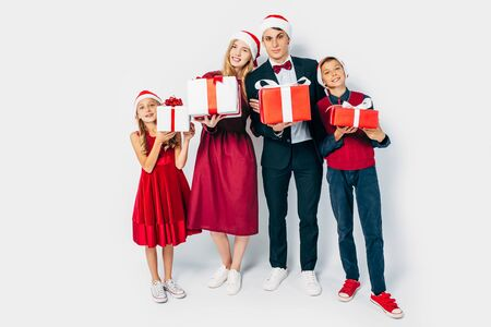Young happy Christmas family with kids, in Santa hats, holding Christmas gifts in hands on white background. New Year, Christmas, holiday