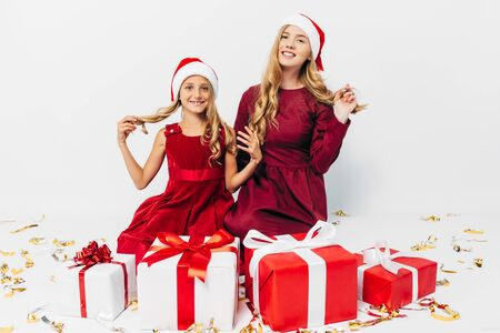 Young Christmas family, mom and daughter in Santa hats having fun with Christmas gifts, on white background. New Year, Christmas, holiday