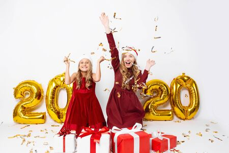 Happy excited mom with a little daughter, in Santa hats, cheerfully sitting on a white background with balloons in the form of numbers 2020, with Christmas gifts, throwing festive confetti. Christmas, New year, 2020
