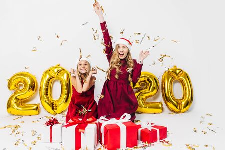 Happy excited mom with a little daughter, in Santa hats, cheerfully sitting on a white background with balloons in the form of numbers 2020, with Christmas gifts, throwing festive confetti. Christmas, New year, 2020 写真素材