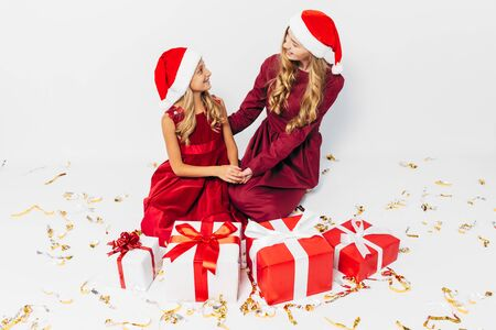 A young Christmas family, mom and daughter in Santa hats, spend time together sitting with Christmas gifts, on a white background. New Year, Christmas, holiday 版權商用圖片