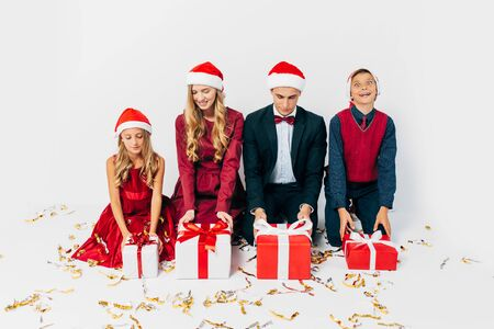 Young happy Christmas family with kids wearing Santa hats while sitting opening Christmas gifts, on white background. New Year, Christmas, holiday
