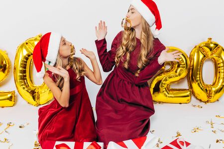 Merry Christmas!. Cheerful mom and her cute daughter in Santa hats. A parent and a small child have fun with Christmas gifts on a white background, with balloons in the form of figures 2020. Christmas And New Year