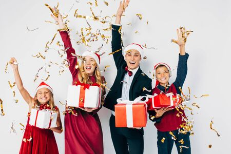 A young happy Christmas family with children dressed in Santa hats is having fun with Christmas gifts in hand, tossing confetti on a white background. New Year, Christmas, holiday