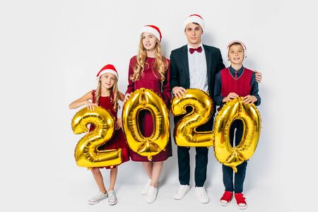 Young happy family with kids wearing Santa hats holding balloons shaped like numbers 2020 on white background. New year, Christmas, holiday 写真素材