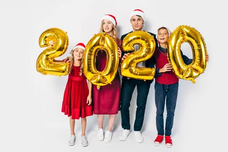 Young happy family with kids wearing Santa hats holding balloons shaped like numbers 2020 on white background. New year, Christmas, holiday Фото со стока