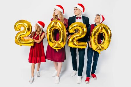Young happy family with kids wearing Santa hats holding balloons shaped like numbers 2020 on white background. New year, Christmas, holiday 版權商用圖片