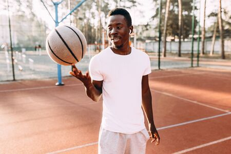 Basketball player spins a basketball ball in the stadium