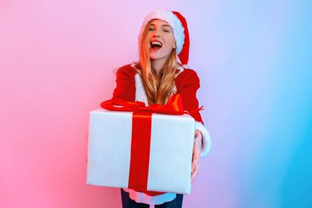 Cheerful young woman in Santa hat, gives Christmas gift with ribbon. A beautiful girl looks into the camera. Standing in the background with red and blue neon light