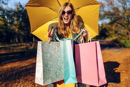 A curious young woman in a coat and with a yellow elegant umbrella, on the street after shopping, looks into a bag. Autumn shopping