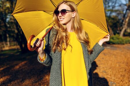 Stylish elegant girl, in a coat and with a yellow umbrella, posing in the Park among the trees with orange leaves. Autumn time Stockfoto