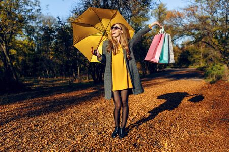Stylish young girl, in a coat and with a yellow umbrella, in the Park after shopping, with bags in her hands. Autumn shopping