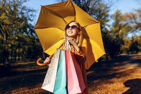 Stylish happy young girl, in a dress and with a yellow umbrella, in the Park after shopping, with bags. Autumn shopping