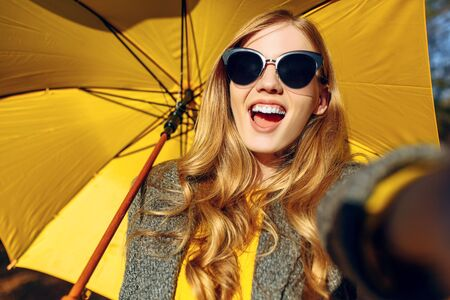 Happy girl in sunglasses and with yellow umbrella taking selfie in autumn Park. Autumn time Stockfoto