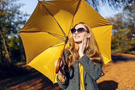 Happy young girl wearing warm coat with yellow umbrella walking in Park with yellow leaves, autumn time