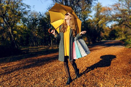 Happy elegant young girl with umbrella and shopping bags in the Park, blonde enjoys a new purchase on the background of autumn foliage. Autumn shopping, shopping, autumn fashion