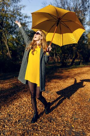 Happy stylish girl in coat and with yellow umbrella walking in Park with autumn leaves. Autumn time