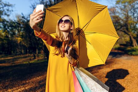 A stylish young girl, with a yellow umbrella, takes a selfie on her smartphone on the street after shopping and holding bags. Autumn shopping Stockfoto