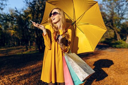 An elegant beautiful young girl, with a yellow umbrella, uses a mobile phone while walking down the street, and holds bags. Autumn shopping