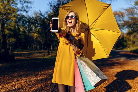 Stylish happy girl with yellow umbrella on the street, holding shopping bags, showing a blank mobile phone screen. Autumn shopping Stockfoto