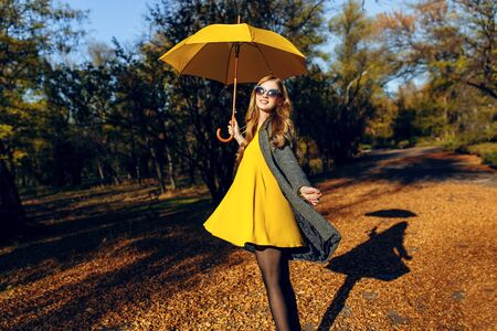 Happy young girl in autumn stylish clothes, spinning in the autumn Park. A joyful girl enjoys a walk in the forest among the trees with orange leaves. Stockfoto