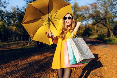 Stylish happy young girl, in a dress and with a yellow umbrella, in the Park after shopping, with bags shows a gesture of victory and success. Autumn shopping Stockfoto