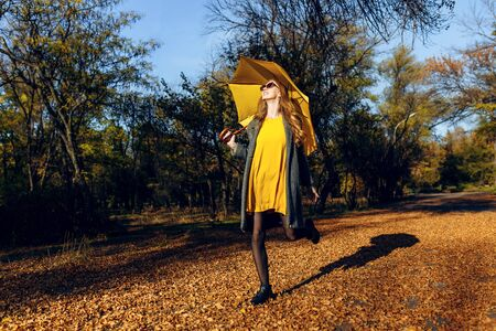 Happy excited stylish girl, in a coat and with a yellow umbrella, runs through the Park with yellow leaves. Autumn time