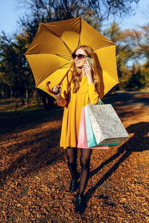 Stylish beautiful young woman in a dress with a yellow umbrella, in the street holding colorful shopping bags and talking on a cell phone. Autumn shopping Stockfoto