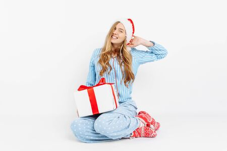 Christmas morning. Happy beautiful young girl, in Christmas pajamas and Santa hat, opens Christmas gift, on white background Stockfoto